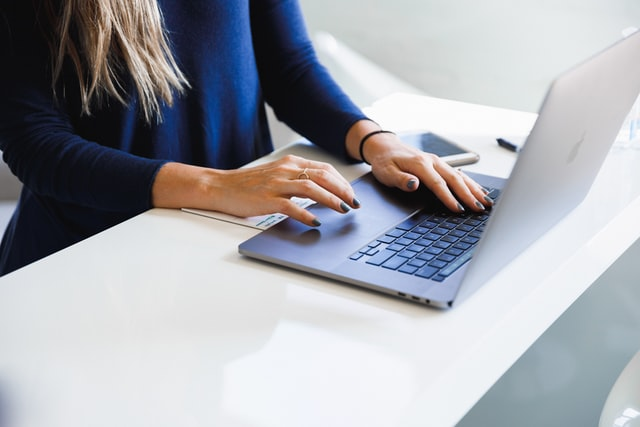 A women typing on a laptop