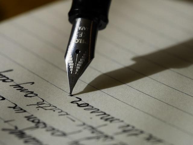 Pen writing cursive on paper
